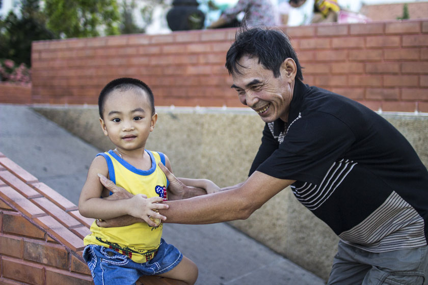 A grandfather steadies his grandson at play. Family is such an important aspect of Vietnamese culture.