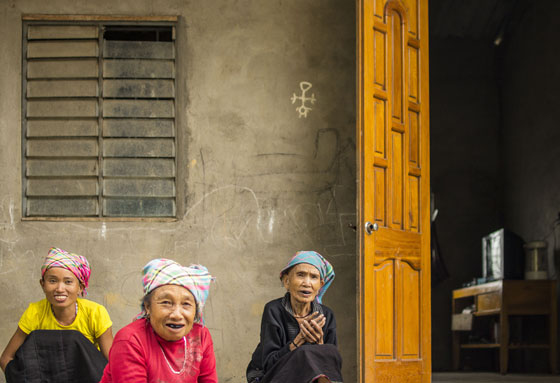 Three generations of Lao Lu women. In Lao Lu culture, a black smile is considered a sign of beauty, so women dye their teeth black using vegetable dyes, while men dye their teeth red. Younger generations, however, no longer practice this tradition.
