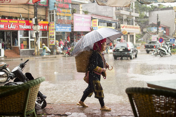 A Red Dao woman navigates the wet streets of Sapa.